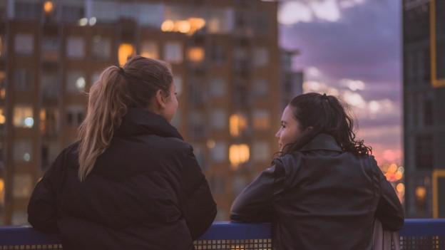 Zwei Frauen, die über ein Geländer schauen