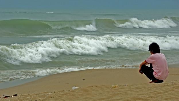 Ein junger Mann in der Hocke, vor ihm das Meer in Wellen