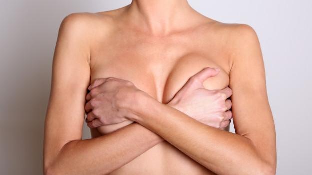 Eine Frau deckt mit ihren Händen ihre Brüste ab