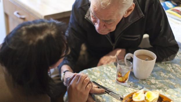 Frau hilft älterem Mann beim Frühstück.