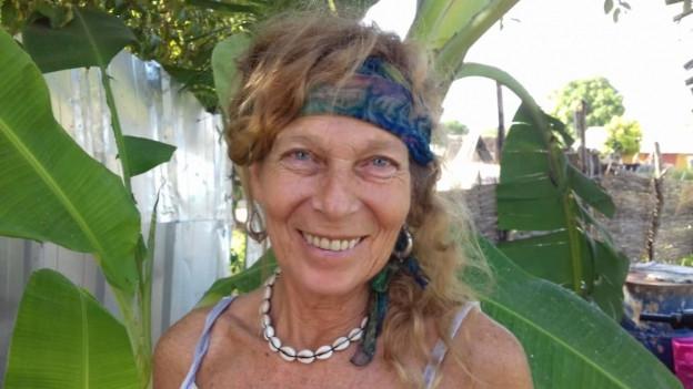 Marielle Furter steht vor einer Palme. Sie trägt eine Kette aus Muscheln.