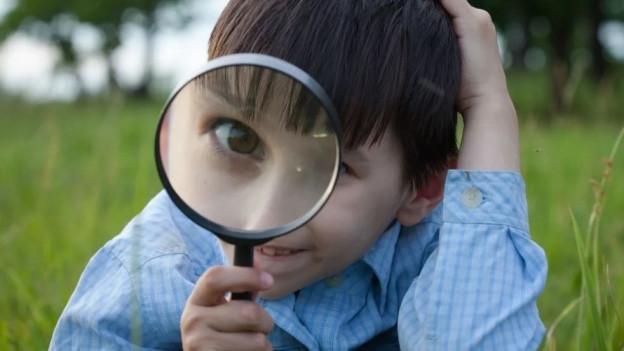 Ein Bub blickt durch ein Vergrösserungsglas,sein Auge ist daher riesengross