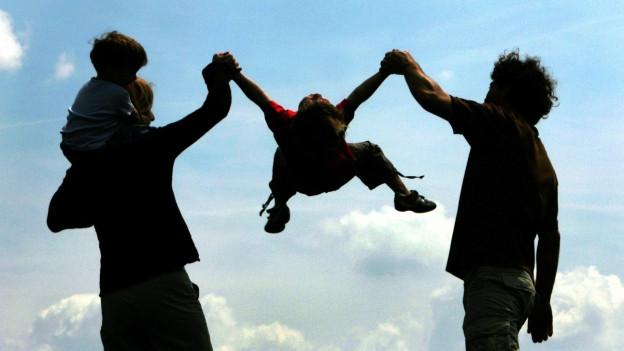 Ein Kind wird von seinen Eltern an seinen Armen hochgeschwungen
