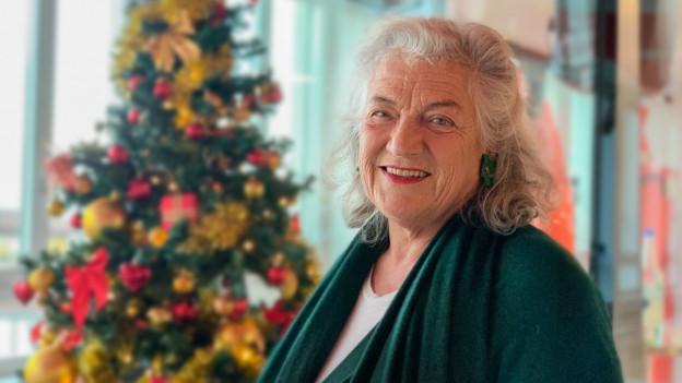 Frau Ringier steht vor dem Weihnachtsbaum und lächelt.