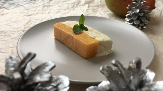 Mango-Vanille-Glacé mit Meringues-Crunch auf einem Teller angerichtet.