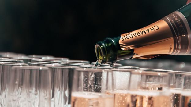 Gläser werden mit Champagner gefüllt