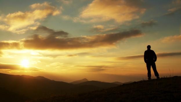 Eine Person steht auf einem Berggipfel und blickt in den fernen Sonnenuntergang.