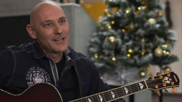 Liedermacher Walti Dux mit Gitarre vor einem Weihnachtsbaum