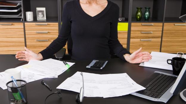 Blick auf einen Bürotisch mit viel Papier