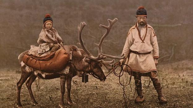Ein Kind auf einem Rentier, daneben steht der Vater und hält das Rentier.