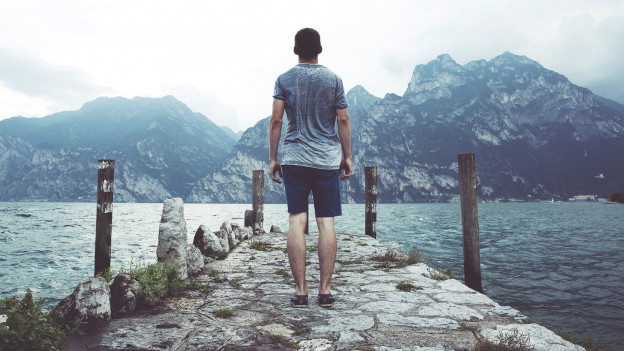 Mann steht auf Steinweg am See und schaut in die Ferne.