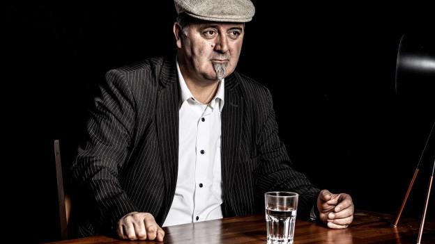 Roberto Brigante sitzt an einem Tisch, vor ihm ein Glas Wasser