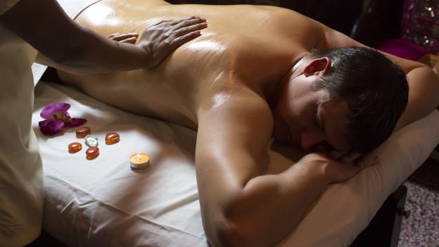 Mann auf dem Bauch liegend bei Massage