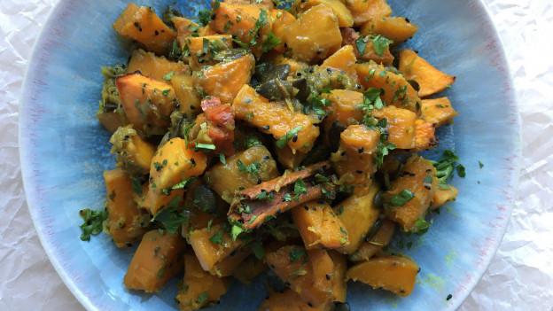 Kürbisstücke mit Kürbiskernen und vielen orientalischen Gewürzen im Ofen geschmort.