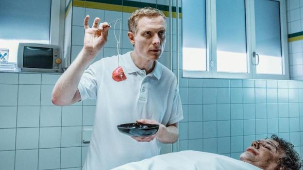 """Alois Semmelweis, der Rechtsmediziner in der Fernsehserie """"Der Bestatter"""", im weissen Kittel hält bei einer Autopsie mögliche Hinweise in die Höhe."""