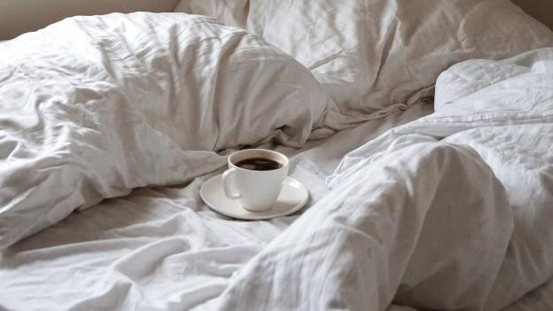 Bett mit einer Tasse Kaffee