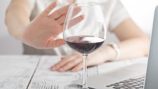 Eine Frauen weist ein Glas Weisswein mit abwehrender Geste von sich.