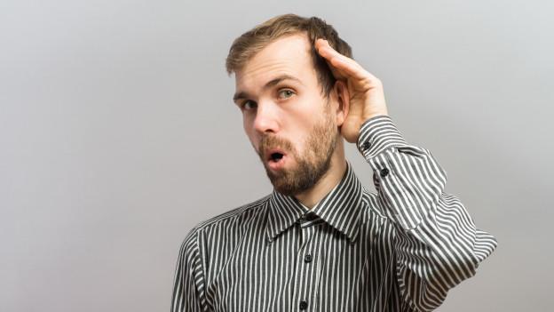 Ein Mann hält sich genau lauschend die Hand ans Ohr.