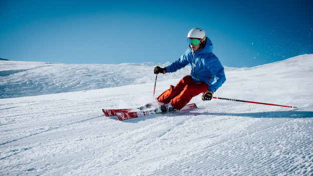 Ein junger Mann fährt rasant auf den Skiern
