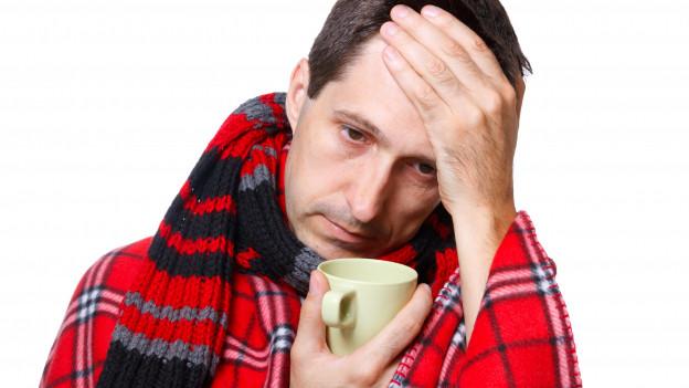 Mann mit Grippe hält eine Tasse Tee.
