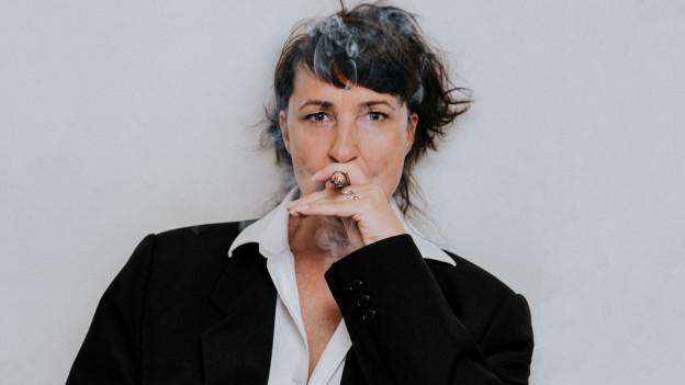 Claudia Sabitzer trägt einen Herrenanzug und raucht eine Zigarre.
