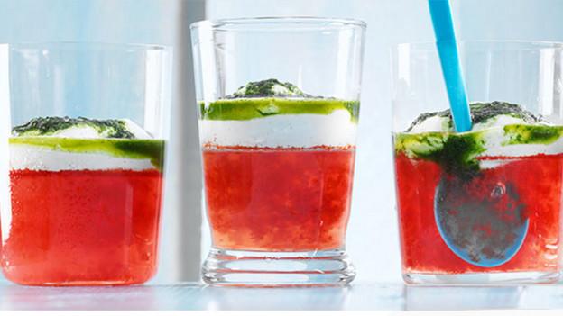 Drei Gläser Melonensaft, garniert mit Basilikum.