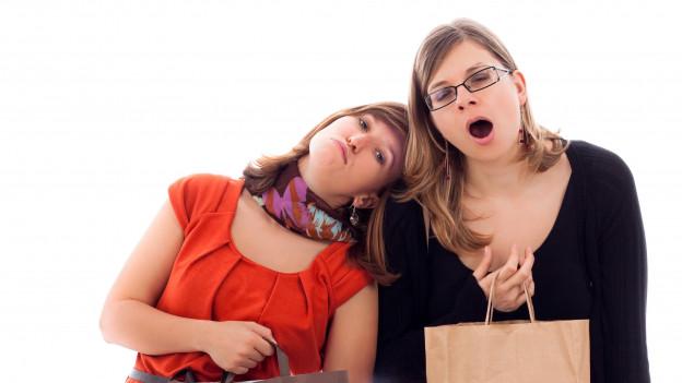 Zwei Freundinnen, eine gähnt und stützt sich auf die andere.