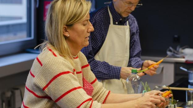 Eine Frau und ein Mann beim Gemüse rüsten und schneiden