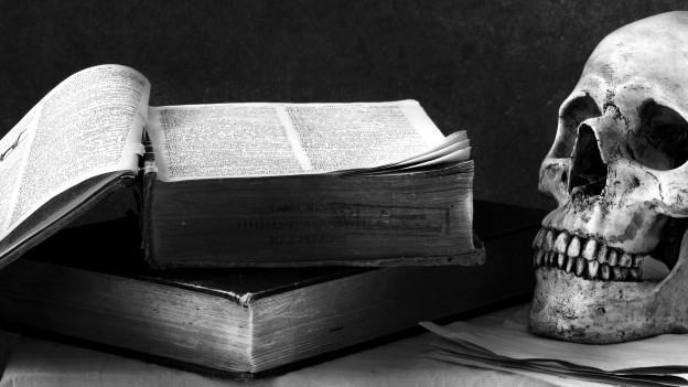 Aufgeschlagenes Buch und Menschenschädel