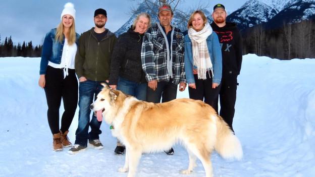 Das Bild zeigt Familie Saurer mit Hündin Molly draussen im Schnee in Kanada.