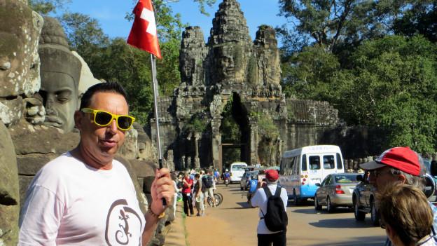 Hubi Aeschbach steht mit einer kleinen Schweizer Flagge in der Hand vor einem Tor aus Stein in Vietnam.