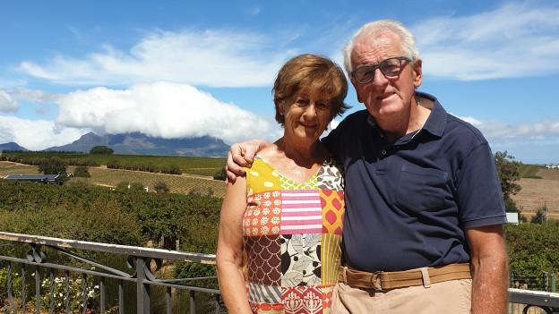 Das Bild zeigt Rosmarie und Fred Rüst vor ihren Weinreben in Stellenbosch in Südafrika. Die Sonne scheint.