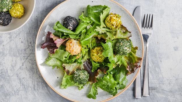 In Nüssen gewendete Ricotta-Pralinen auf einem Salatteller.