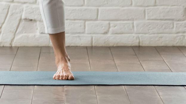 Frau steht auf Yoga-matte.