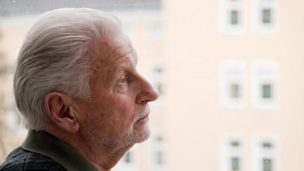 Ein älterer Mann schaut traurig, einsam aus dem Fenster.