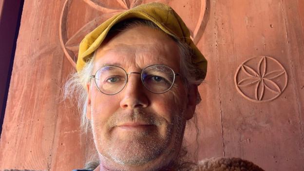 Das Bild zeigt Linard Bardill. Er trägt eine Brille und eine Mütze.