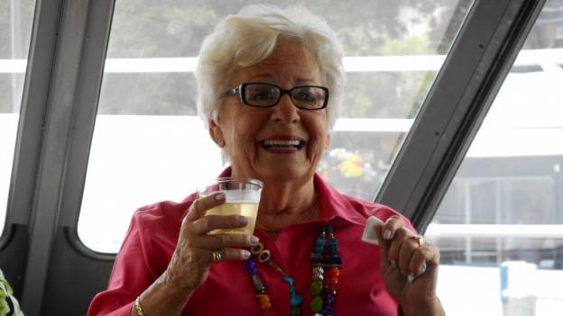 Elsa Olson lachend mit rosa Hemd und bunter Perlenkette