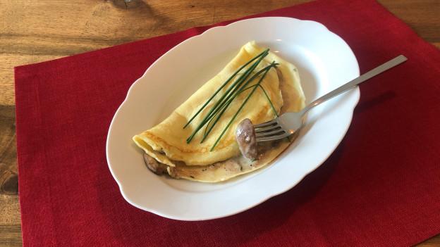 In einem weissen Teller hat es eine Omelette mit Champignos-Füllung.