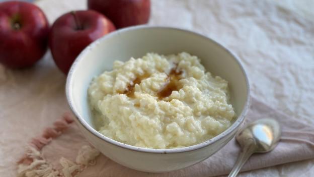 Eine Schale mit Milchreis mit Apfel und Ahornsirup.