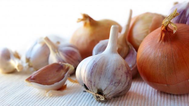 Zwiebeln und Knoblauch liegen auf einer hellen Unterlage.