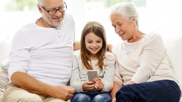 Ein Mädchen guckt ins Smartphone, während zwei weissharige Personen darauf blicken.