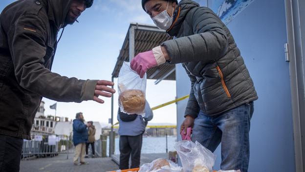Das Bild zeigt einen Mann eines Hilfswerks in Genf, der einer bedürftigen Person einen Sack mit Brot gibt.