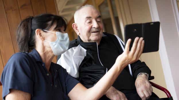 Eine Pflegefachfrau mit Maske betreut einen Altersheimbewohner