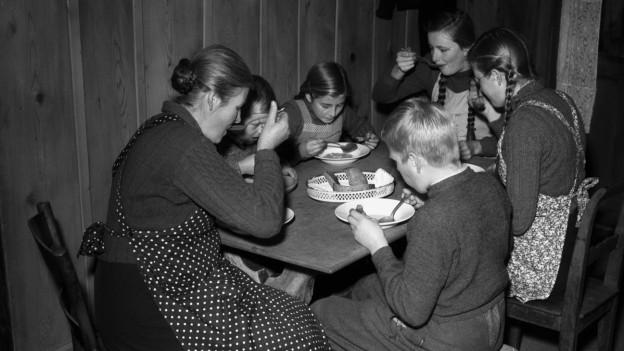 Familie isst nach dem Krieg zusammen am Tisch.