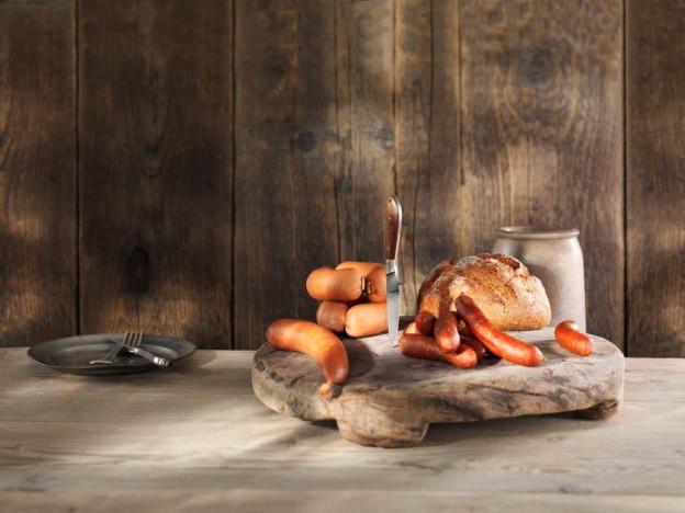 Auf einem Holzbrett liegen verschiedene Würste und Brot.