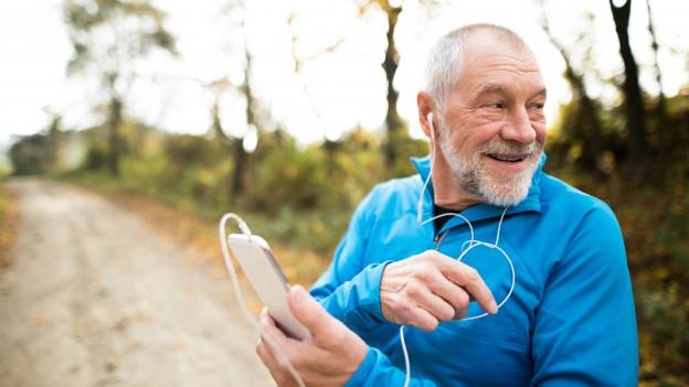Älterer Herr läuft mit Handy