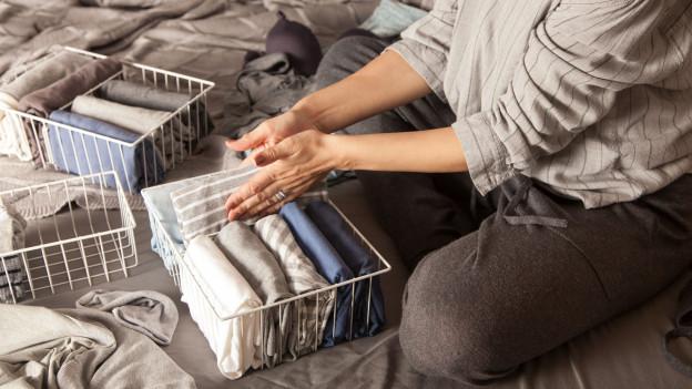 Eine Person faltet zerknitterte Wäsche säuberlich zusammen und verstaut sie in einem Korb.