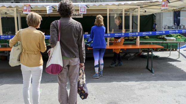 Kunden warten vor einem Stand am Berner Wochenmarkt auf dem Waisenhausplatz mit der nötigen Distanz.