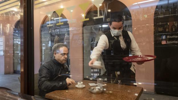 Ein Kellner mit Maske bedient einen Kunden im Restaurant