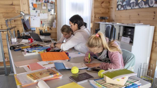 Eine Mutter und ihre Töchter sitzen zuhause am Pult. Die Kinder lernen.